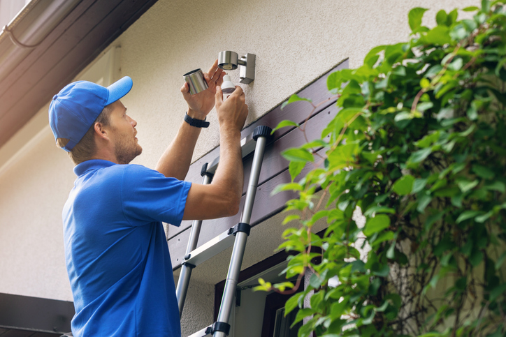 Electrician on ladder changing light bulb in outdoor lighting fixture
