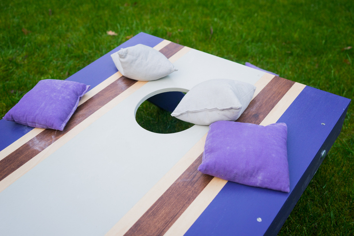Close-up of blue and white bean bag toss game with purple beanbags