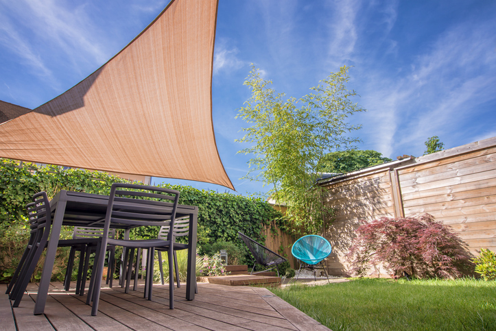 Tan shade sail positioned over patio dining set in fenced backyard